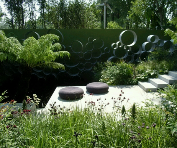 Minimalist-Backyard-Outdoor-Garden-with-Fresh-Green-Plants-Decorating-and-Two-Soft-Rounded-Cushions-Accessories-also-Round-Pattern-Wall-for-Modern-Garden-De-resized