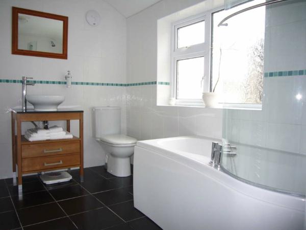 carrelage-mural-pour-la-salle-de-bain-un-commode-en-bois-et-une-baignoire-céramique