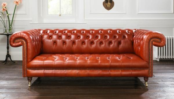 canapé-de-cuir-vintage-bouffant-rouge-sur-un-plancher-de-bois