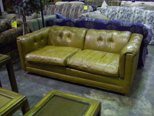 canapé-de-cuir-vintage-vert-dans-un-hall-plein-de-meubles