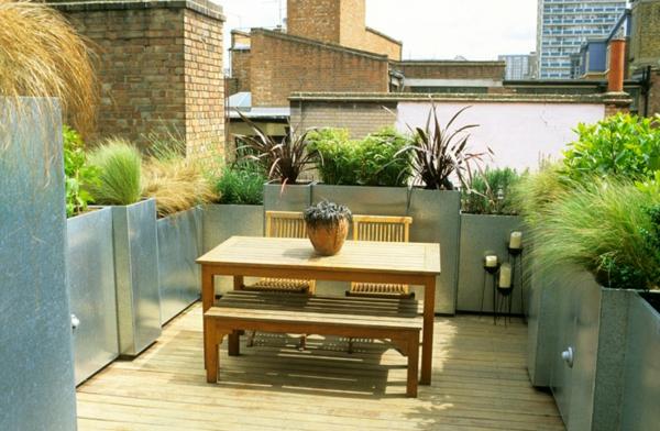 terrasse-sur-toit-jardin-avec-grands-pots-de-fleurs-en-acier-et-une-table-de-bois