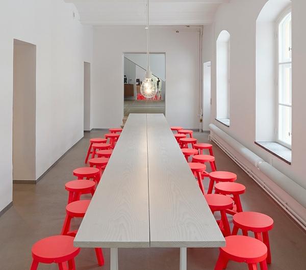 un hall long comme couloir avec des chaises de trois pieds autour d'une table blanche et longue