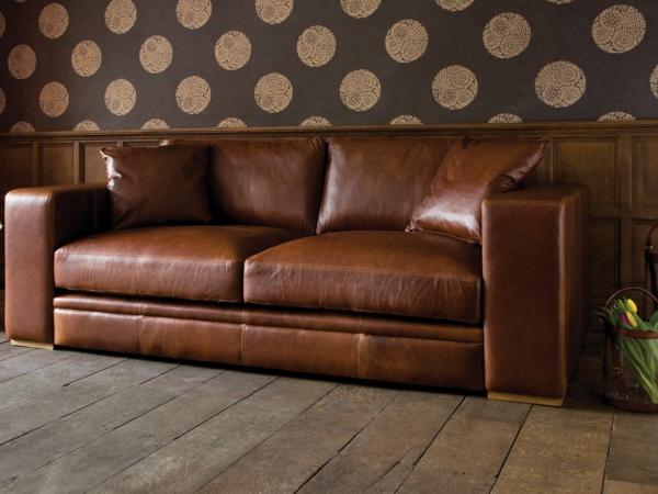 canapé-de-cuir-vintage-près d'un mur-avec-papier-peint-intéressant