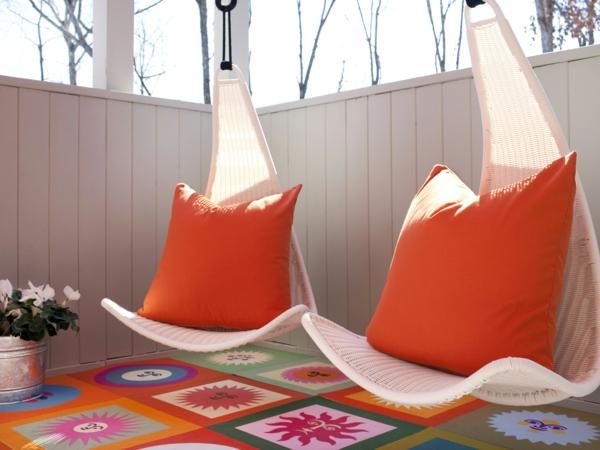 chaise-suspendue-chaises-blanches-et-des-coussins-oranges-au-dessus-d'un-tapis-coloré