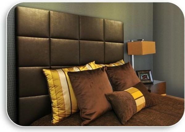 tête-de-lit-capitonnée-noire-et-des-coussins-marronnes-et-jaunes