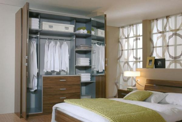 une chambre à coucher avec une armoire à portes pliantes avec miroir