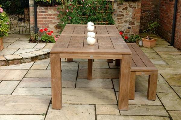 salon-de-jardin-en-teck-une-table-et-une-banquette-dans-une-cour-en-style-ancien