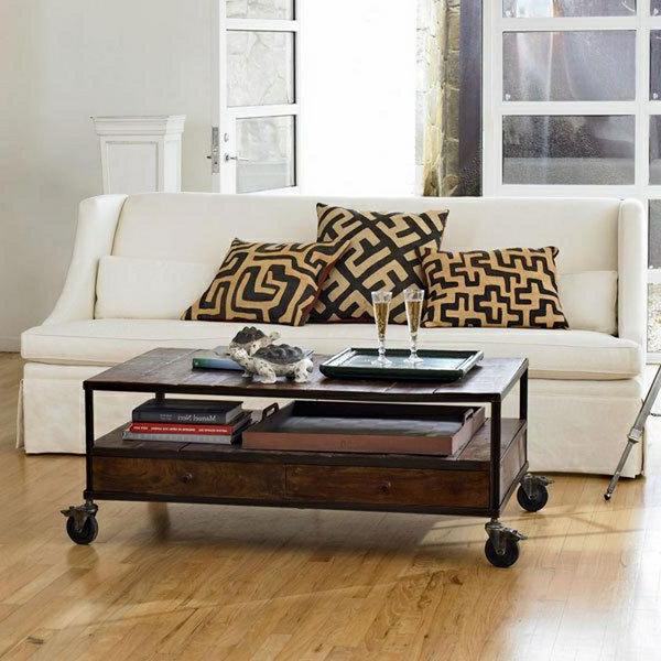 table-basse-industrielle-près-d'un-divan-blanc-et-coussins-décoratives
