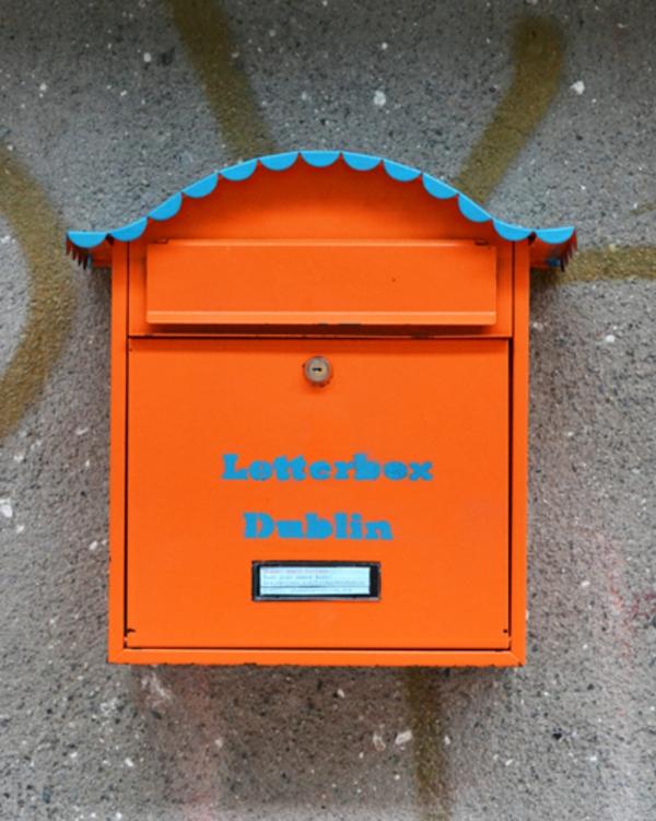 la-boite-en-fer-orange-avec-un-tois-bleu-dans-la-forme-de-maison