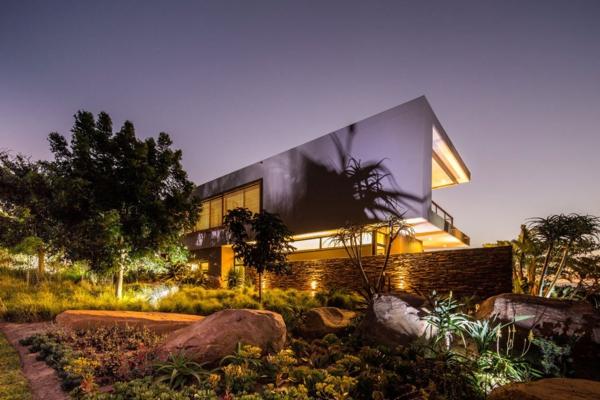 la-maison-contemporaine-avec-un-éclairage-moderne-et-beaucoup-de-verdure-