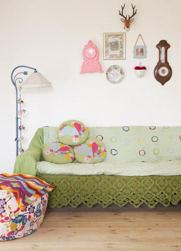 le-canapé-vert-avec-des-beaucoup-des-cousssin-comme-décoration