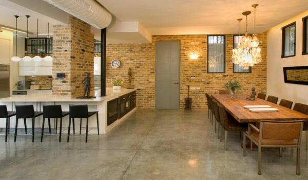 cuisine-ouverte-sur-la-salle-à-manger-grande-table-rectangulaire-et-papier-peint-brique