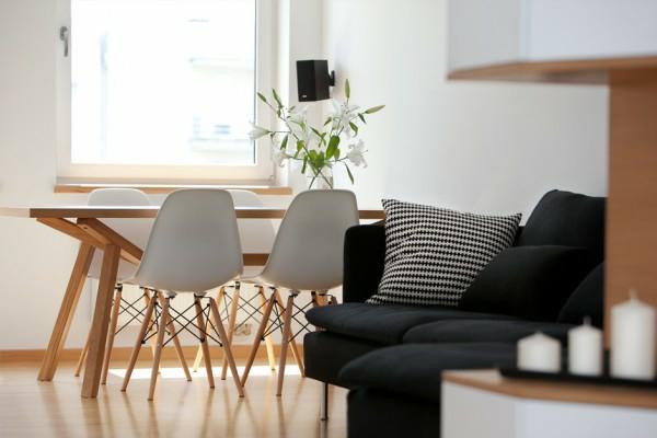 jolie-salle-de-séjour-pour-la-maison-unique-avec-des-chaises-scandinave-et-canapé-noir