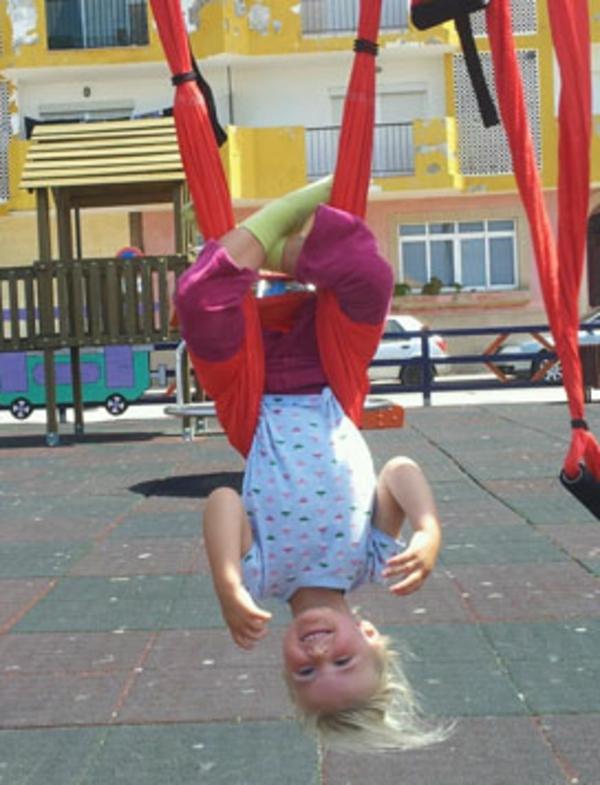 enfant-sur-un-balaçoire-yoga-en-rouge-en-plein-aire