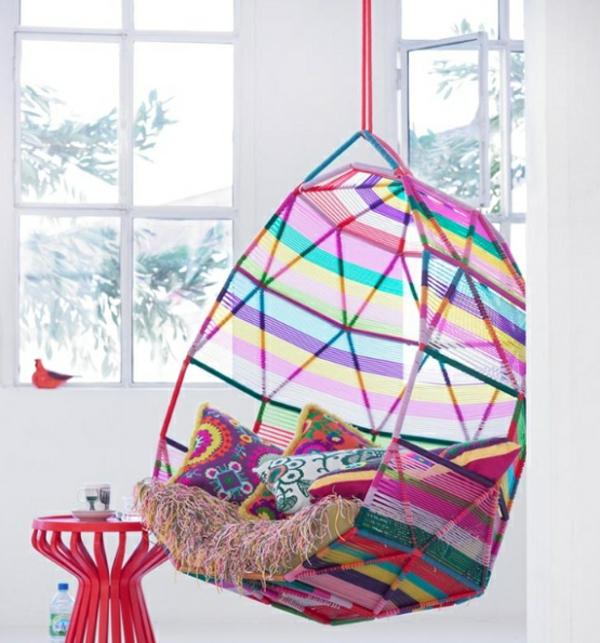 fauteuil-suspendu-multicolore-et-un-tabouret-rouge