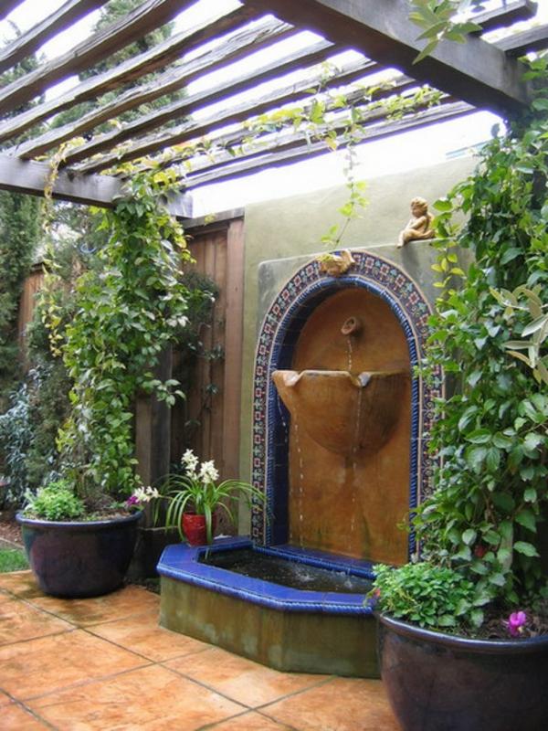fontaine-murale-et-pots-de-fleurs-sous-un-pergola-en-bois