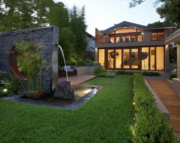 fontaine-murale-extérieur-moderne-une-pelouse-verte-et-allée-en-bois