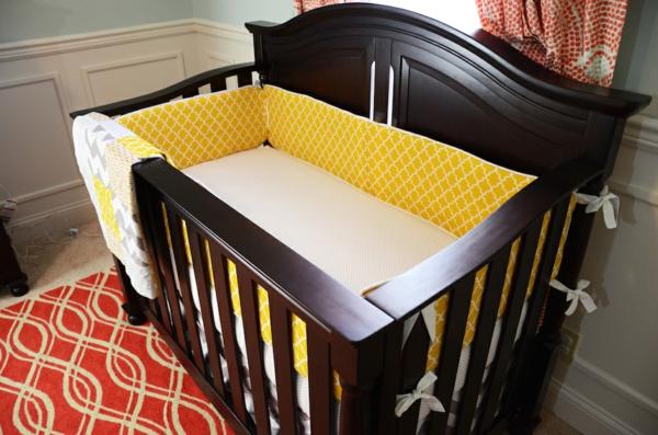 lit-en-bois-avec-un-matelas-en-jaune-et-blanc