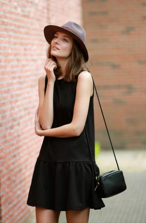 elle-porte-une-jolie-robe-noire-avec-une-purse-noire