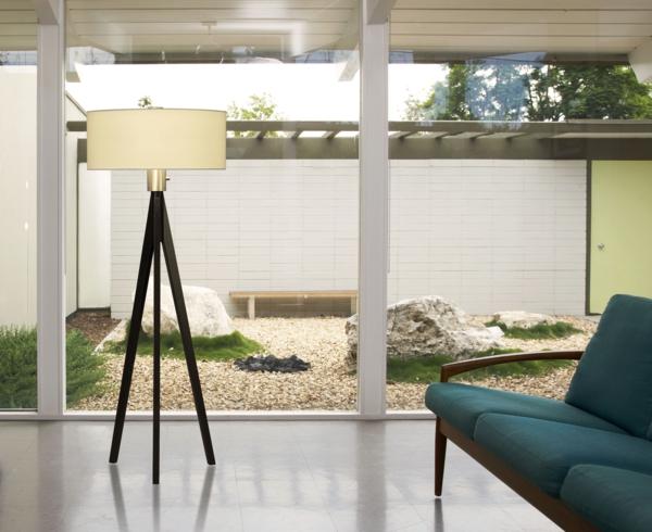 lampadaire-tripode-lampadaire-tripode-près-d'un-grand-mur-transparent
