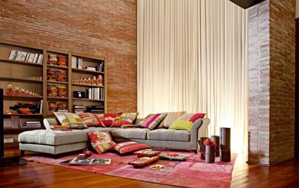 salon-roche-bobois-murs-en-briques-sofa-gris-d'angle-et-un-tapis-rose