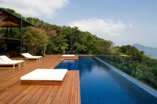 terrase en bois ou composite, grande piscine rectangulaire et chaises