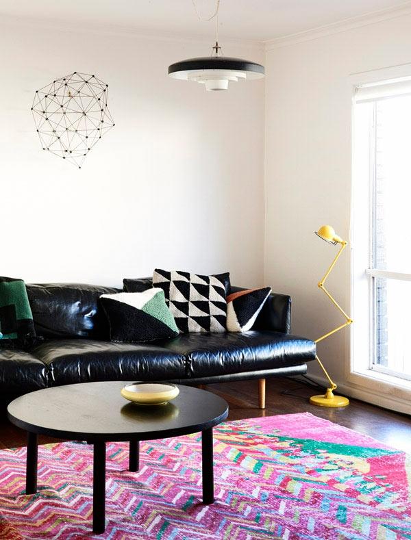 tapis-multicolore-et-sofa-en-cuir-noir