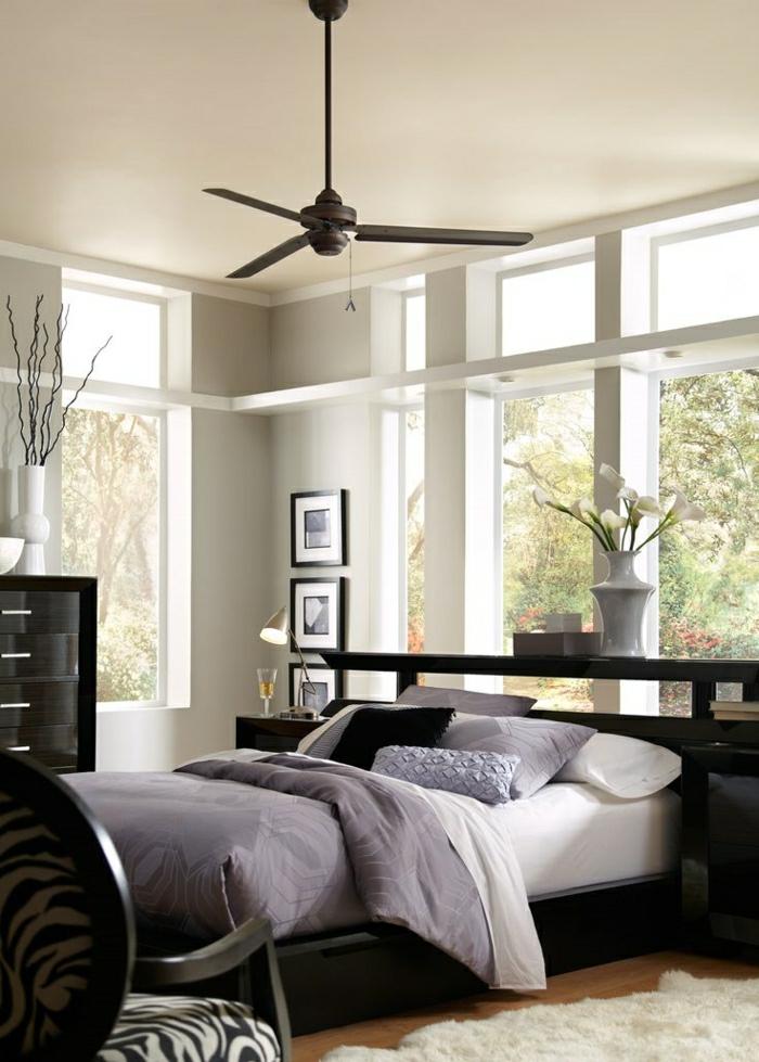 1-chambre-a-coucher-avec-lit-en-bois-foncé-ventilateur-de-plafond-fleurs-chambre-a-coucher