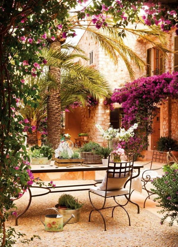 beau-jardin-avec-galets-décoratifs-fleurs-chaises-en-fer-forgé