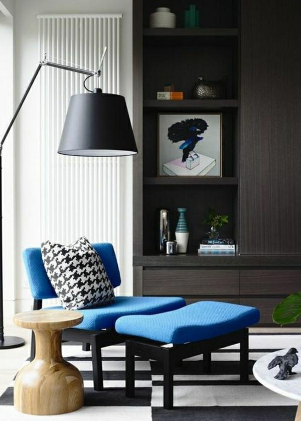 canapé-bleu-avec-lampe-liseuse-noir-tapis-blanc-noir-bibliothèque-commode-en-bois
