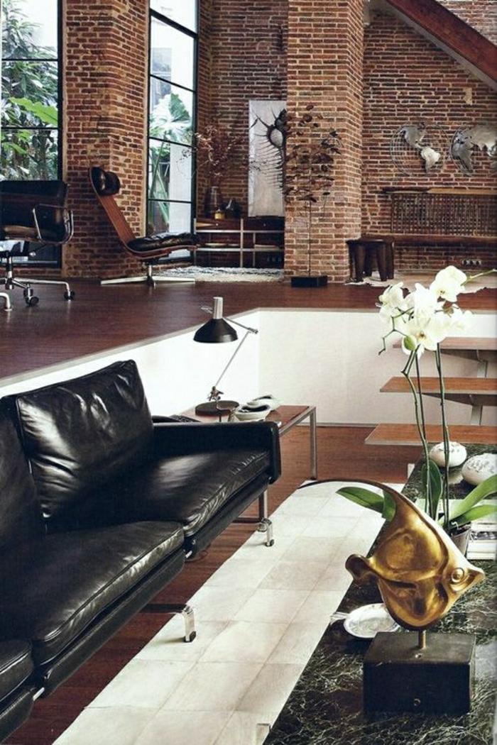 canapé-en-cuir-marron-fleurs-sur-la-table-de-salon-murs-briques-parquet