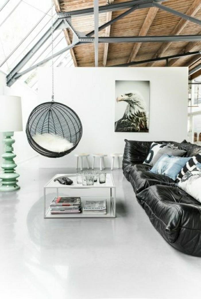 canapé-en-cuir-noir-salon-mansardé-plafond-en-bois-murs-blancs-peintures