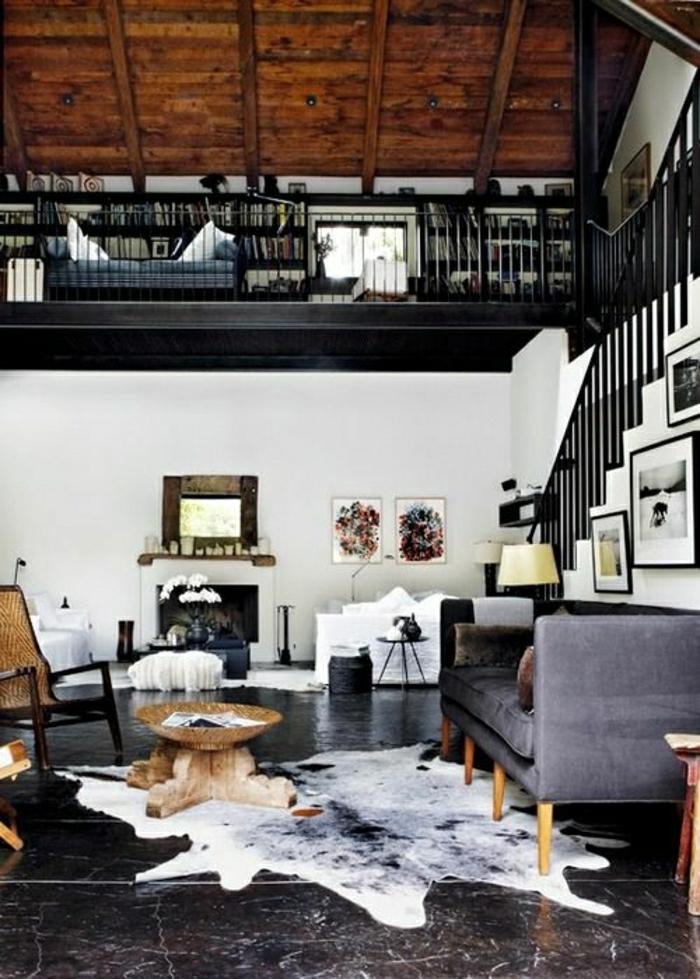 canapé-gris-tapis-en-cuir-carrelage-noir-plafond-haut-mansardé-carrelage-noir-petite-table-de-salon