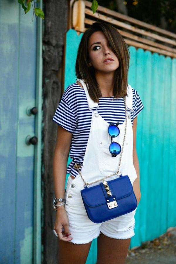 combishort-en-jean-blanc-avec-lunettes-de-soleil-sac-bandoulière-bleu-lunettes-de-soleil