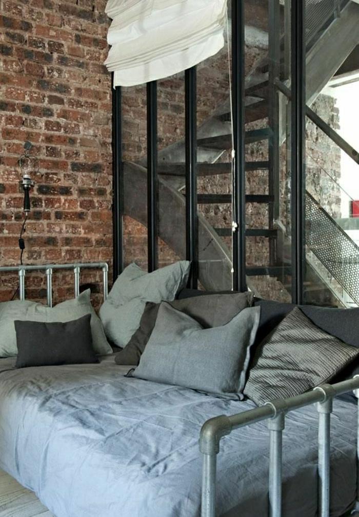 escalier-en-fer-chambre-a-coucher-mur-de-briques-linge-de-lit-gris-coussins