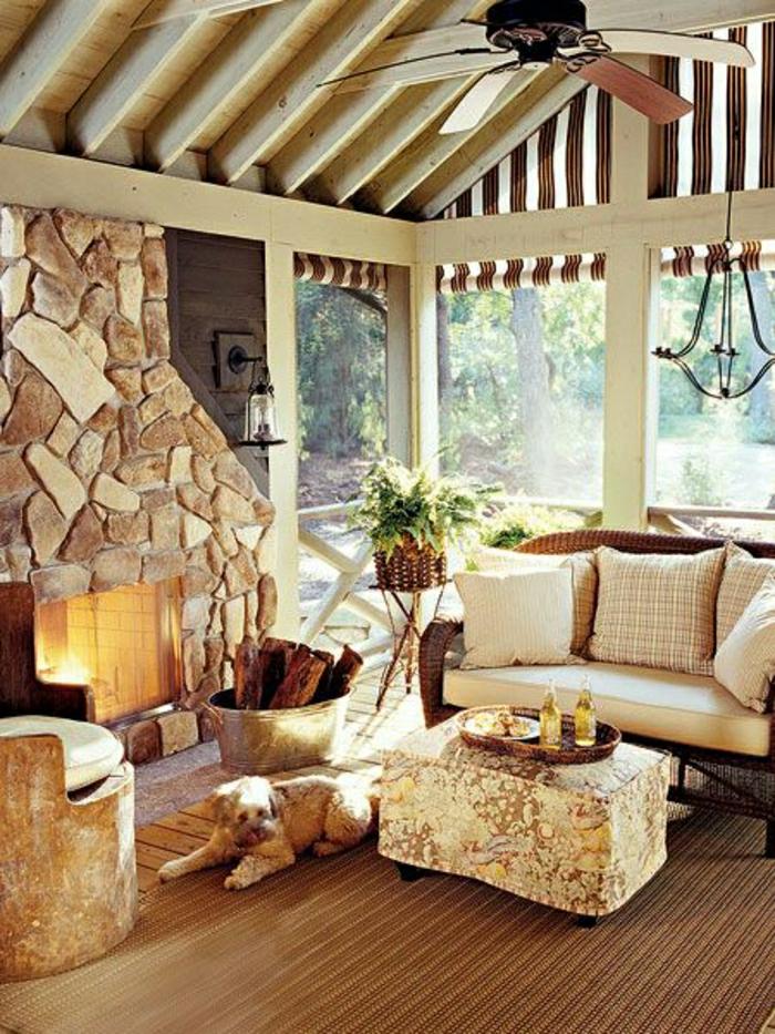 la-plus-belle-véranda-avec-un-ventilateur-de-plafond-cheminée-en-pierre-fenetres-grandes