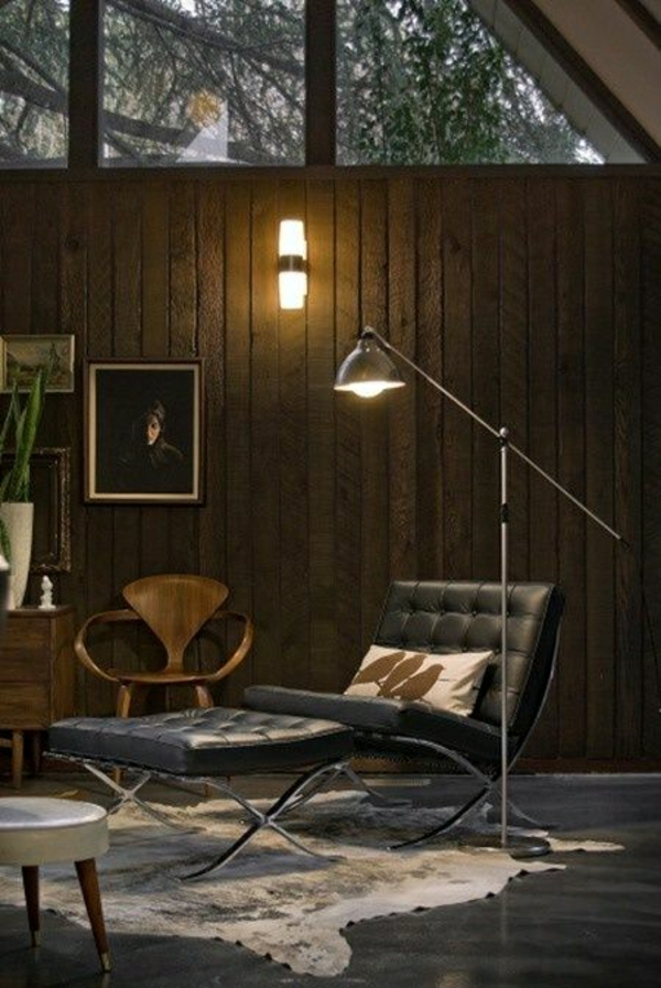 lampe-de-lecture-en-fer-canapé-en-cuir-noir-murs-en-bois-peintures-sol-en-lin