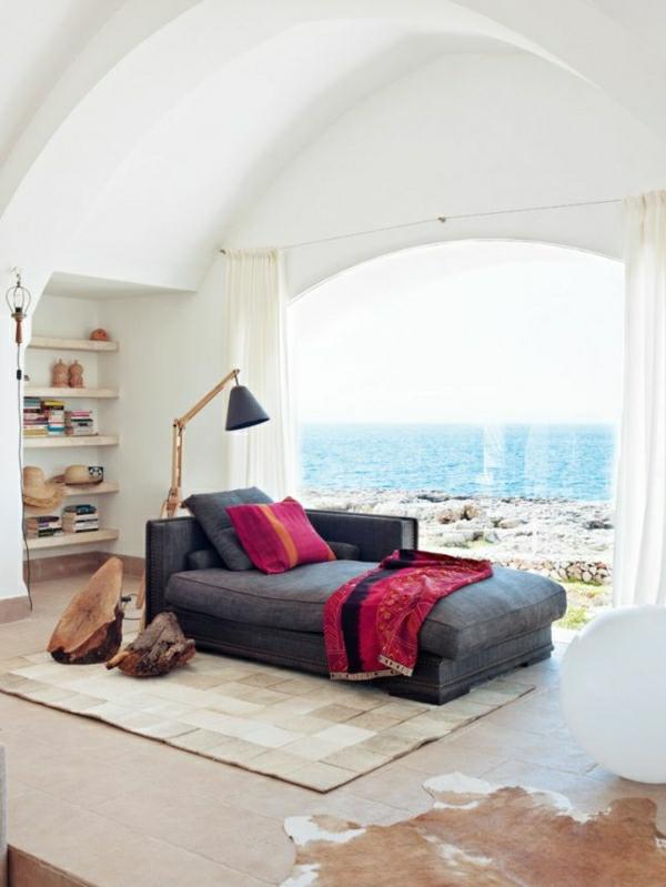 lampe-liseuse-a-poser-fauteuil-gris-grande-fenetre-belle-vue-océan-tapis-en-cuir-carrelage