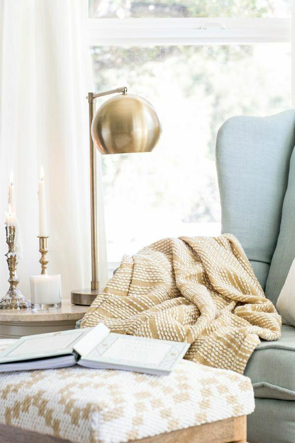 lampe-liseuse-or-fauteuil-gris-bleu-petit-commode-en-bois-bougies