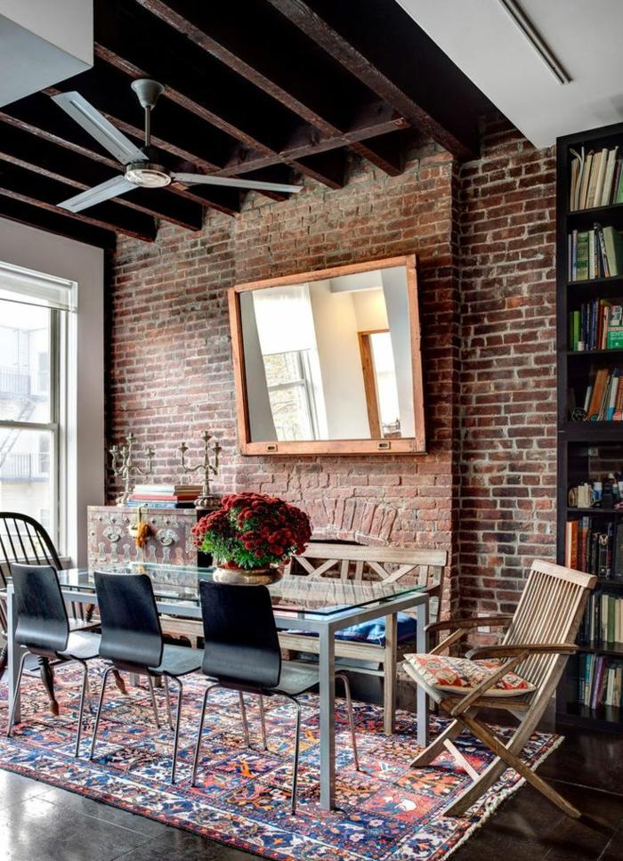 mur-en-brique-table-en-verre-et-acier-et-tapis-multicolore