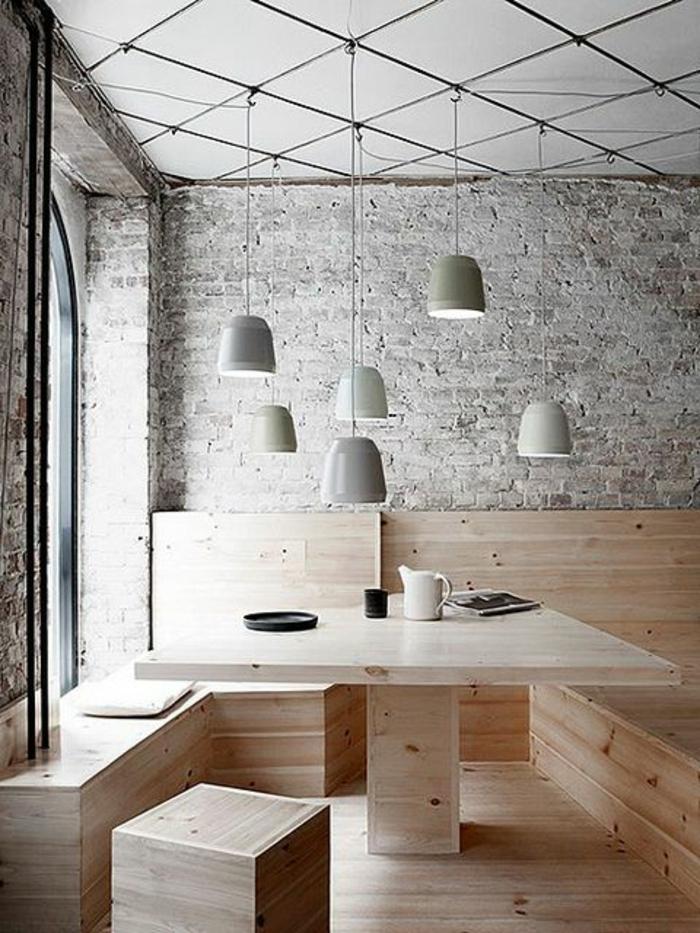 mur-en-brique-une-table-et-banquettes-en-bois-et-lampes-pendantes