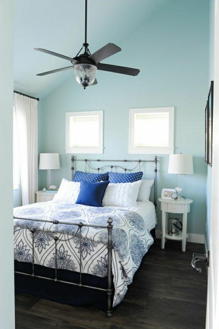murs-bleus-coussins-colorés-lit-en-fer-forgé-table-de-nuit-en-bois-blanc