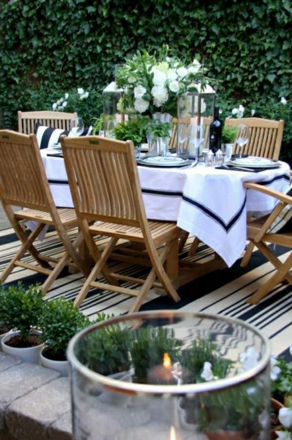 nappe-blanche-noir-table-de-jardin-en-bois-chaises-en-bois-jardin-extérieur-haie-vive