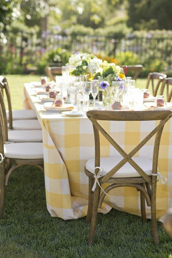 nappe-jaune-blanche-aux-carreaux-décoration-de-table-de-fleurs-chaises-rustiques-en-bois