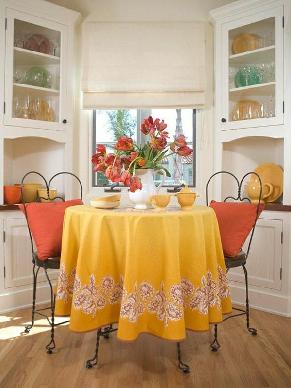 nappe-jaune-de-table-chaises-en-fer-forgé-fleurs-de-table-fenetre