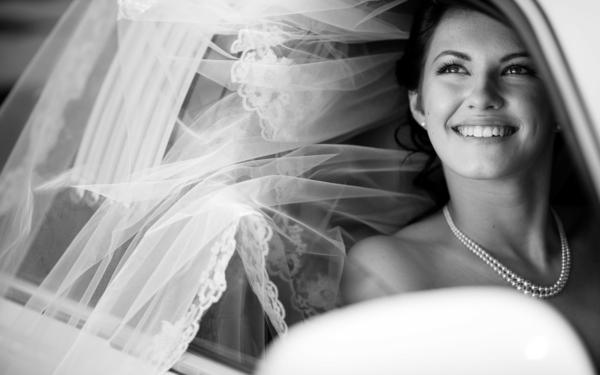 photographie-noir-et-blanc-portrait-mariée-robe-sourire-perles-jolie