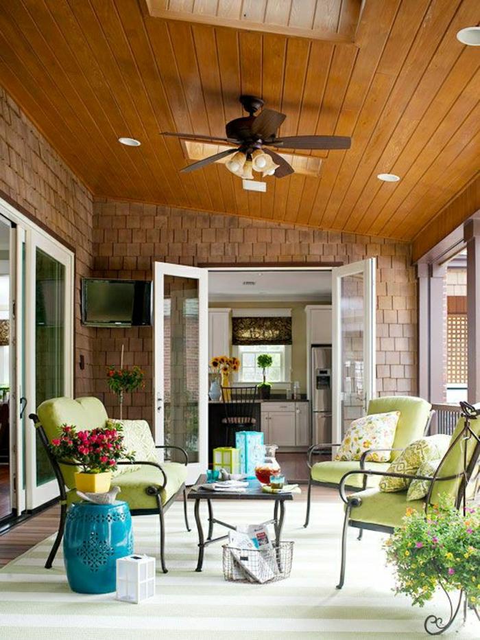 porch-avec-ventilateur-lustre-insolite-toit-en-bois-chaises-en-fer-forgé-verts-maison-extérieur