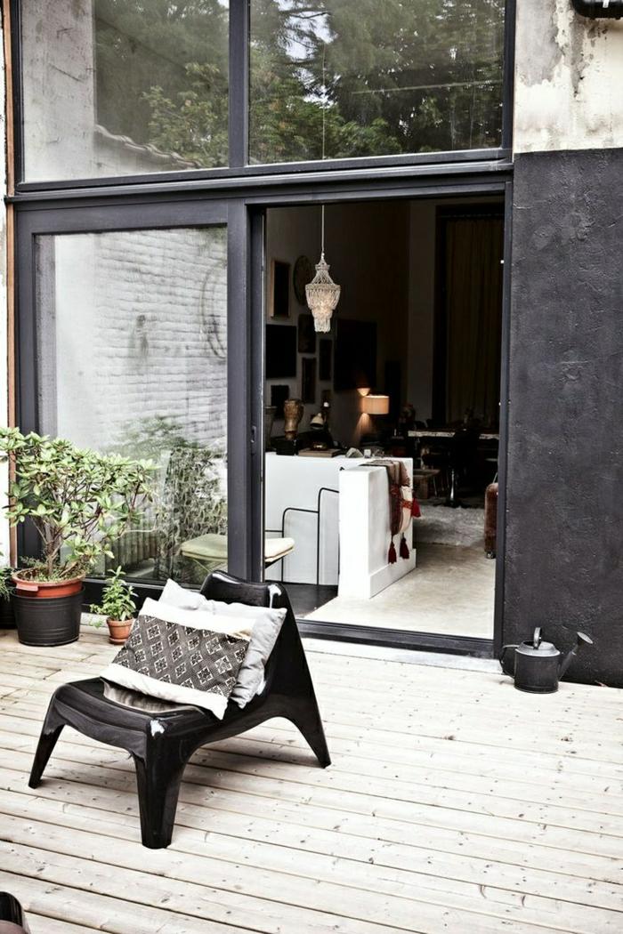 porte-coulissante-d-extérieur-chaise-plastique-noire-sol-en-bois-plantes-vertes