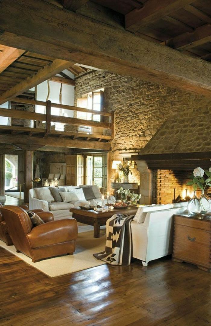 salon-en-cuir-blanc-marron-cheminée-mur-en-pierre-fleurs-décoration-mur-en-pierre-parquet