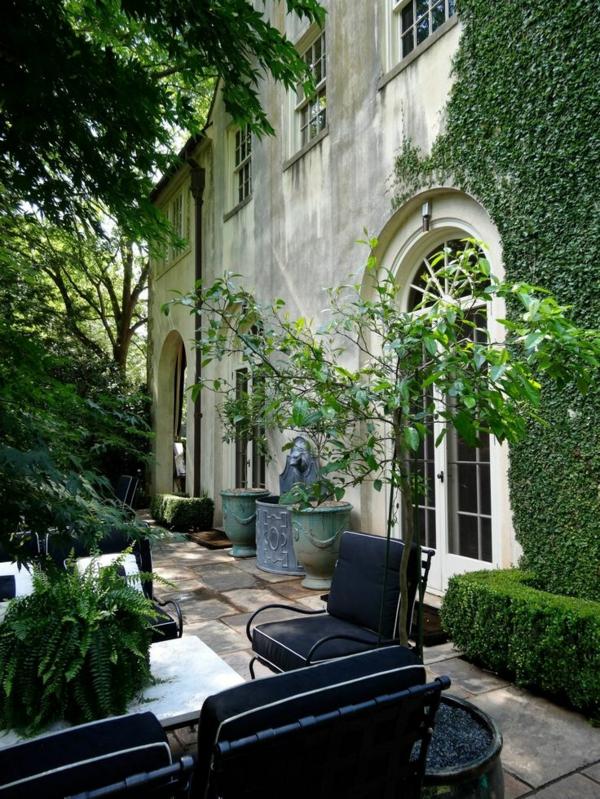 tables-de-jardin-chaises-arbres-maison-grande-haie-vive